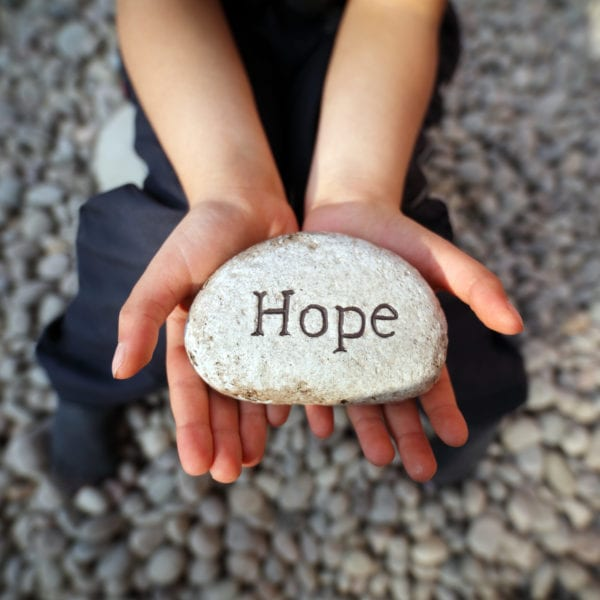 Child on a beach with hands cupped holding stone pebble with the word hope engraved concept for faith, love, spirituality and religion